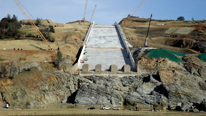 Cranes sit on the sides of the Oroville Dam spillway in November 2017. Water officials and the construction manager said hairline cracks on the spillway are normal and expected in reinforced concrete because it shrinks as it cures.