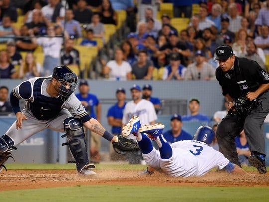 Chris Taylor slides past Brewers catcher Manny Pina