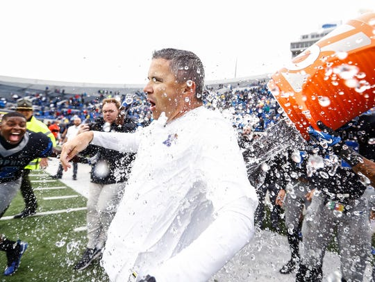 Memphis head coach Mike Norvell (middle) gets a dumped