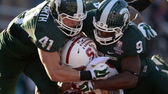 Michigan State linebacker Kyler Elsworth (41) and safety Isiah Lewis (9) tackle Stanford running back Tyler Gaffney (25) in the 100th Rose Bowl.