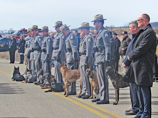 State troopers stand at attention with their K-9 partners on Lowe Road in Big Flats during a memorial ceremony for slain state Trooper Andrew J. Sperr.