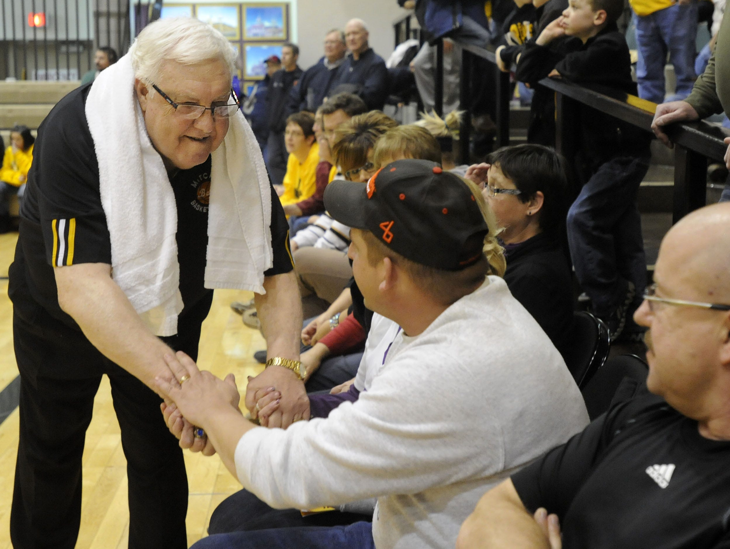 Mitchell High School boys basketball head coach Gary Munsen (left) greets fans and friends after he was honored at the Corn Palace on Feb. 14, 2012, in Mitchell, S.D. Munsen died Jan. 12, 2016.