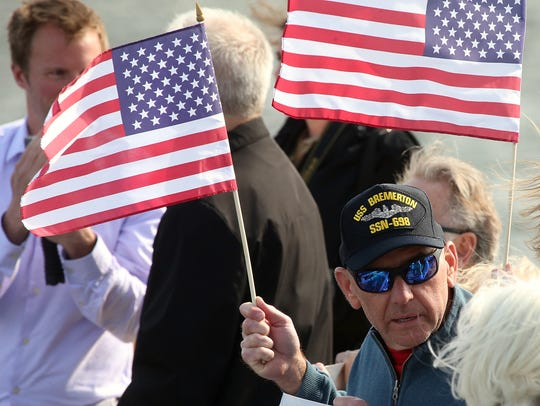 Ted Magee, of Baton Rouge, Louisiana, wears his USS Bremerton hat while waving a flag along the pier at Naval Base Kitsap-Bremerton on Friday. Ted's son serves aboard the submarine.