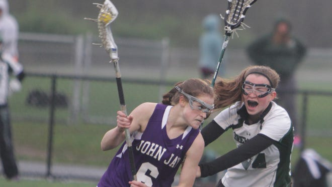 John Jay's Cara O'Reilly attempts to drive past Brewster's Dana Lestrange during a girls lacrosse game at Brewster on Friday. John Jay won 9-6.