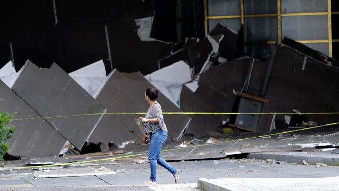 A pedestrian walks near debris on the driveway of the Atlantic Club Casino after part of the ceiling collapsed, Wednesday, Sept. 27, 2017, in Atlantic City, N.J.