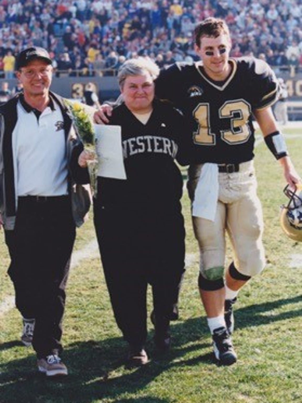Tim Lester walks off the field at Waldo Stadium with his parents, Fred and Pat Lester, during Senior Day in 1999.