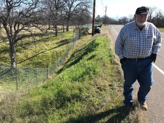 Patrick Duffin walks along Olinda Road near a section of his fence he said is being damaged because of erosion created after Shasta County widened the road.