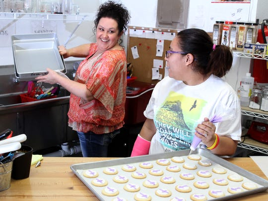 Crystal Jacquez-Aguilar, back, and Teanna Maes work at Nutty Buddies on Thursday.