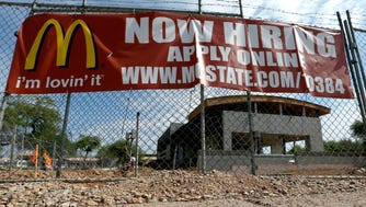 """A """"Now Hiring"""" sign hangs in front of a McDonald's under construction in Tempe, Ariz."""