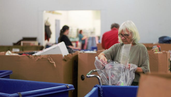 Connie Rehm, sorts through donations in the warehouse of a Goodwill on Marion-Mount Gilead Road. Representatives of Goodwill, like many nonprofit organizations, are worried that the new tax plan signed in December will eliminate the tax incentive to donate to charitable causes.