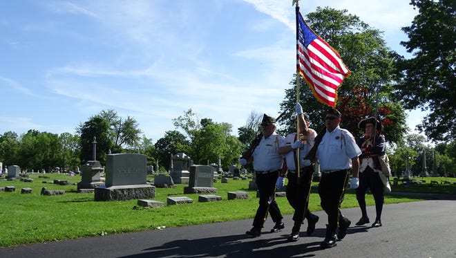 The color guard marches into Oakwood Cemetery during the 2016 Memorial Day Parade.