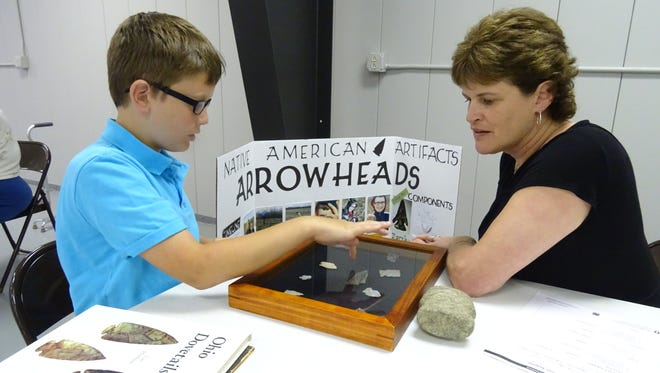 Isaiah Bender, left, 10, of Bucyrus, shows judge Vicki Hartschuh his arrowhead 4-H project Thursday during judging at the Crawford County Fairgrounds.