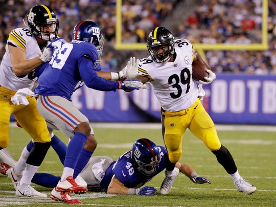 Steelers running back Terrell Watson (39) tries to avoid Giants defenders during a preseason game on Aug. 11. The Oxnard High graduate made the Pittsburgh roster as a backup running back and a special-teams standout.