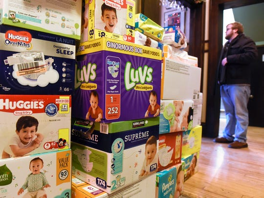 In this file photo, Operation Baby New Year organizer Justin Michael watches as more donations of diapers roll at Pioneer Place on Fifth in St. Cloud.