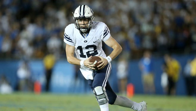 Quarterback Tanner Mangum of the BYU Cougars scrambles against the UCLA Bruins on Sept. 19, 2015, in Pasadena, California.