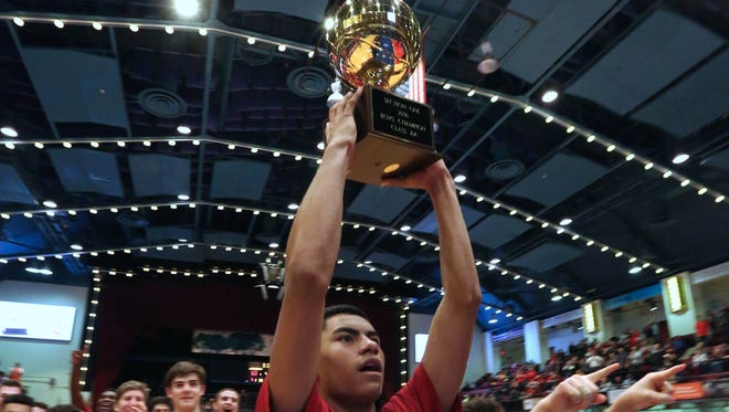 Fox Lane's Alex Olsen holds up the gold ball trophy after his team upset Mount Vernon to win the 2016 Section 1 Class AA championship at the County Center.