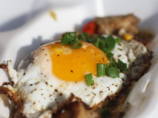 Garnished with scallions, a fried egg tops a to-go