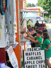 Children accept free samples at one of the food vendors
