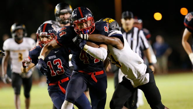 Peoria Centennial linebacker-turned-ballcarrier John Rincon breaks a tackle attempt by Scottsdale Saguaro's Calvin Williams and runs for a touchdown at Glendale Community College in Glendale on Thursday, Aug. 27, 2015.