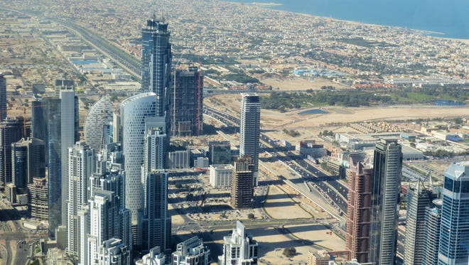 View from the 124th floor of the Burj Khalifa with the iconic Burj Al Arab Hotel visible in the distance.