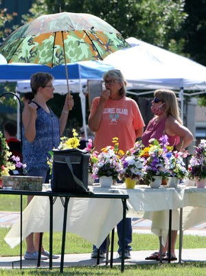 Renae Hughart, from left, Lesa Suttles and Tammy Hanna chat between themselves, Saturday, June 6, 2020, on the Greenwood Square during the first day of the Greenwood Farmers Market.