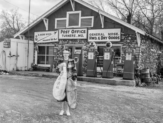Gertrude Murrell, postmaster at Turners, holding a