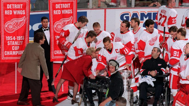 At the Red Wings banner-raising ceremony, owner Mike Ilitch, left, looks on as his wife, Marian Ilitch, kisses injured Wing Vladimir Konstantinov on Oct. 16, 1998.