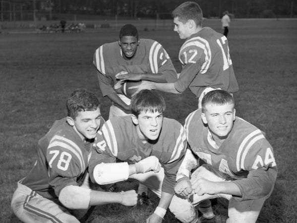 Leon quarterback Billy Sexton (12) hands off in 1966 to running back Leroy Powell, the first African-American to play football for Leon High.