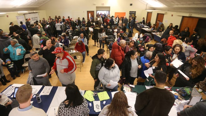 A packed room of families from Puerto Rico attend  welcome reception at the Ibero-American Action League where two dozen agencies came together to provide aid to the families.