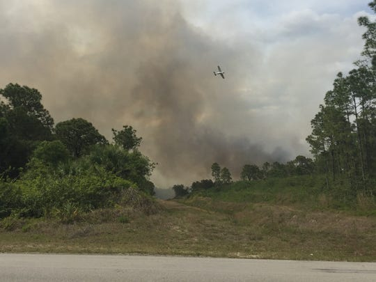 Smoke clouds are visible from the intersection of Andalucia Avenue South and Sunrise Boulevard in Lehigh Acres.  Firefighters are battling a brush fire in the area.