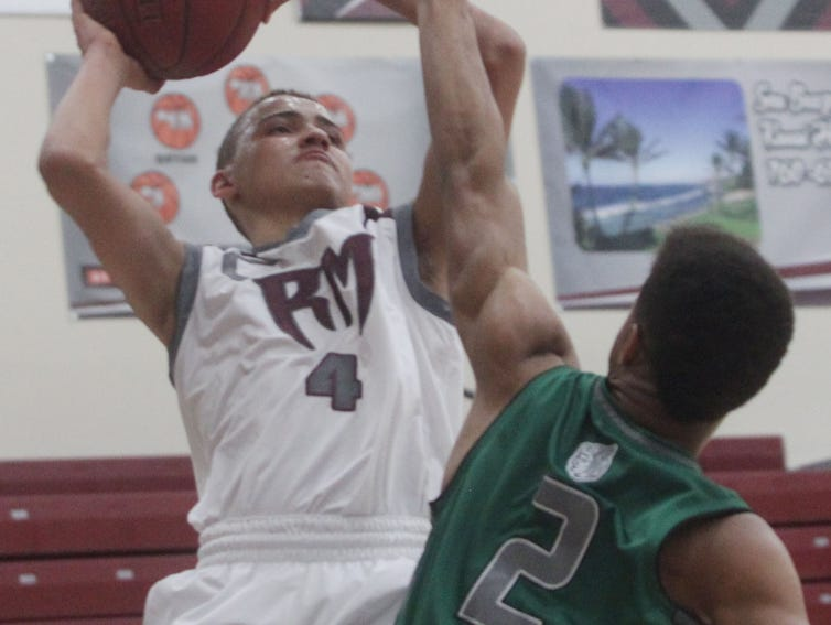 Rancho Mirage High School's Charles Neal tries to make a jump shot as Adam Bell of Twentynine Palms guards him. RMHS won the game.