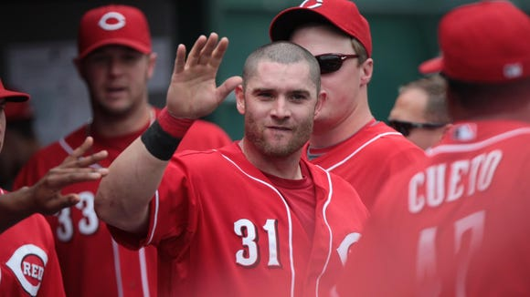 Jonny Gomes is congratulated by teammates in the Reds'