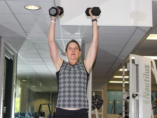 3. Reverse the movement, standing up and pressing the weights overhead.