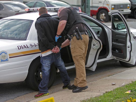 A man is arrested by a New Castle County Police officer off Del. 9 in New Castle on April 25.