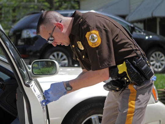 New Castle County Police Officer Michael Zolnowski takes finger prints of a car that was broken in to in Holloway Terrace.