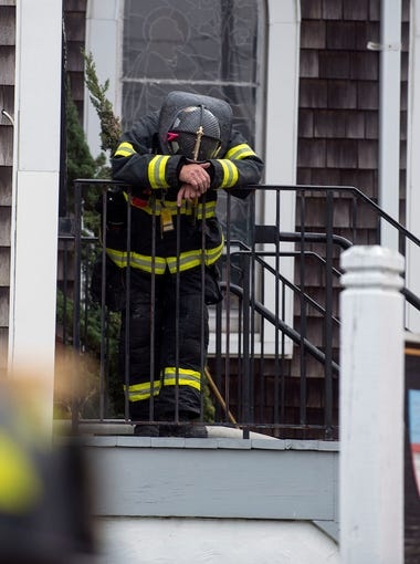 A firefighter leans over the railing outside the entrance of the church after a man lit himself on fire inside the St. Paul's by the Sea church in Ocean City.