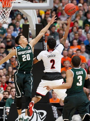 U of L's Quentin Snider, #2, stretches for a score against Michigan State's Travis Trice, #20, during the Elite 8 tournament game in Syracuse, NY.  