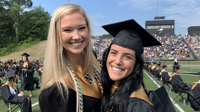 North Augusta High School graduates Saylor Logan, left, and Katie Aleman, right, excitedly await the start of their graduation ceremony at their home football field Thursday.