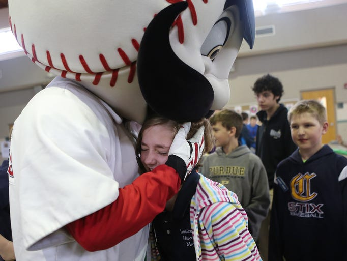 Fifth-grader Elizabeth Granuland is given a hug and kiss by Mr. Redleg as he visits Immaculate Heart of Mary School in Anderson Township on Friday, March 28, 2014.