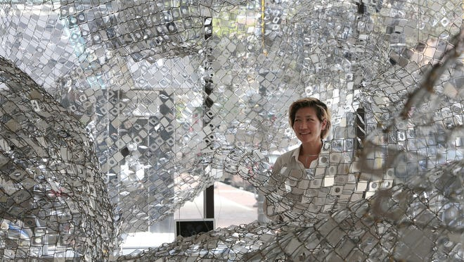 Artist Soo Sunny is seen surrounded by her  'Photo Kinetic Grid Revisited' piece, hanging from the ceiling of the Massachusetts Design Art and Technology Institute (DATMA) gallery at the Star Store building on Purchase Street in New Bedford.