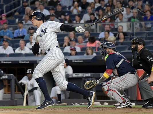 New York Yankees' Aaron Judge, left, hits an RBI-double as Boston Red Sox catcher Sandy Leon,  center, looks on during the first inning of a baseball game Friday, Sept.1, 2017, at Yankee Stadium in New York. (AP Photo/Bill Kostroun)