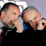 In this Wednesday, Jan. 16, 2013 file photo, Israeli Prime Minister Benjamin Netanyahu, right, and former Foreign Minister Avigdor Lieberman speak during a Likud-Yisrael Beitenu campaign rally in the port city of Ashdod.