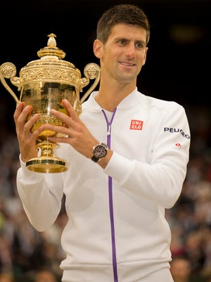 Novak Djokovic poses at the trophy presentation after winning the Wimbledon men's final match against Roger Federer.