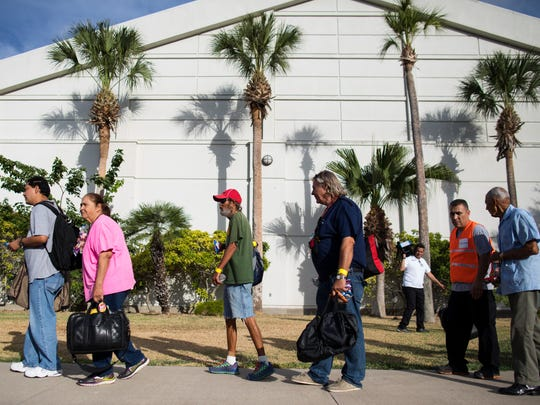 Residents stand in line outside the Corpus Christi Natatorium as they wait to board a bus to evacuate to San Antonio ahead of Hurricane Harvey on Tuesday, Aug. 24, 2017.