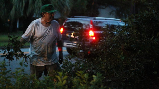 Phil Reuter of Killarney Way prepares to toss away old branches from his property Tuesday evening. He says his property was undamaged and no one from his household was hurt in the day's storms that ravaged the city.