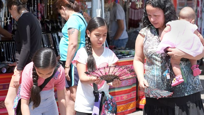People shop the vendors at the annual Cristo Rey Fiesta last year. The annual event celebrating Lansing's Hispanic heritage is the major fundraiser for the church.