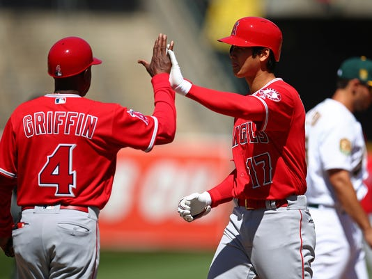 Los Angeles Angels' Shohei Ohtani (17) is congratulated by first base coach Alfredo Griffin (4) after hitting a single in his first major league at-bat against the Oakland Athletics' Kendall Graveman during the second inning of a baseball game on Thursday, March 29, 2018, in Oakland, Calif. (AP Photo/Ben Margot)