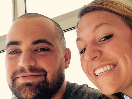Former MSU football player Marcus Calverley and his girlfriend, former Spartan softball player Emma Fernandez, share a smile at an MSU football game.