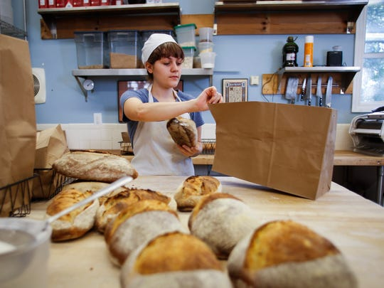 Emily Walkowski of Stone Circle Bakehouse in Holt packages bread for daily deliveries Tuesday, Sept. 5, 2017, at the bakery.  [Matthew Dae Smith/Lansing State Journal]