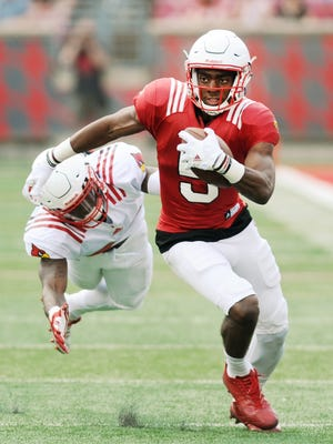 Louisville's Seth Dawkins (5) avoids the tackle attempt by Ronald Walker (in back, left) during the UofL Spring Game on Saturday at Papa John's Cardinal Stadium. April 15, 2017